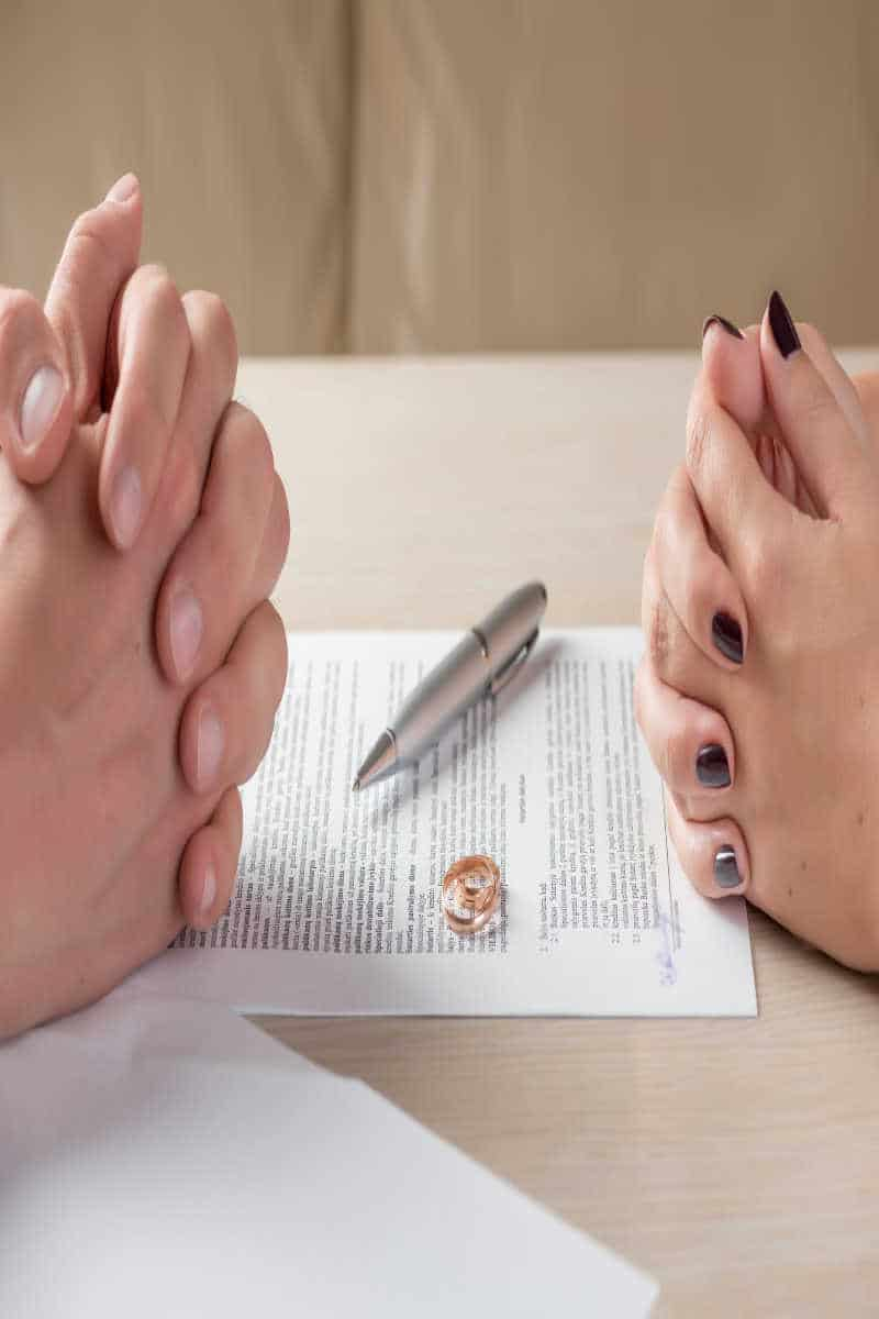 hands of wife and husband signing divorce documents or premarital agreement in Texas. They used DFWPHB to sell their Texas house fast.