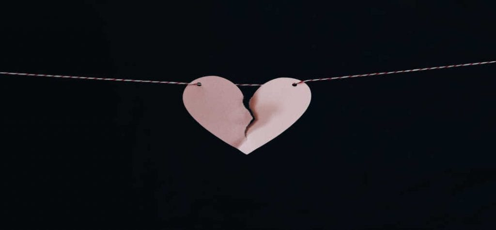 black background with pink broken heart representing divorcing couples in texas