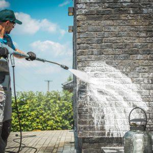 Man power washing his brick house